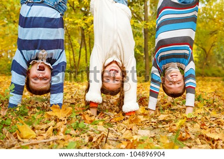 Three  kids upside down in autumn park - stock photo