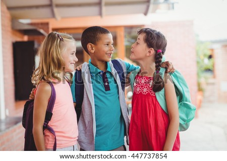 Three kids with arms around each other during the recreation - stock photo