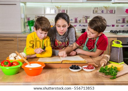 Three kids with food on table reading the cook book, making the dinner together in the kitchen interior