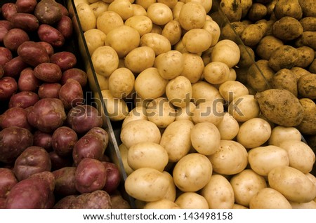 Three kind of fresh potatoes on display in farmers market. - stock photo