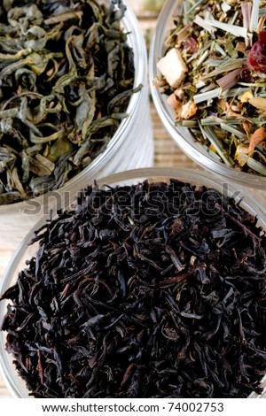 three kinds of dry tea in glasses closeup on straw background - stock photo