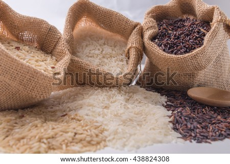 Three kinds of rice in small burlap bags on white background - stock photo