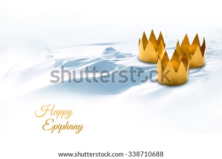 Three King's Day symbolized by three tinkered crowns on a snowy background, text Happy Epiphany - stock photo