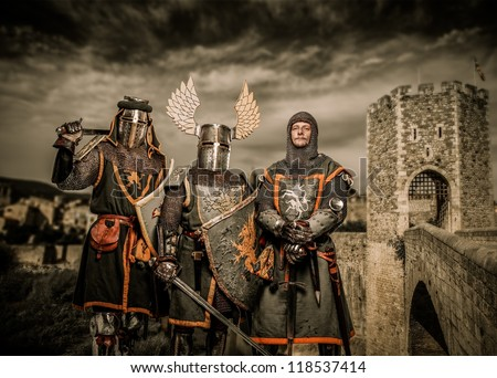 Three knight in armor against Romanesque bridge over river , Besalu - stock photo