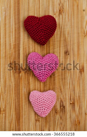 Three knitting hearts on old wooden panel. Background Valentines Day.Valentines day cards. - stock photo