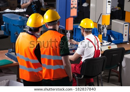 Three labourers in safety helmets are working in factory - stock photo