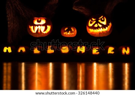 Three large carved pumpkins over a Halloween font - stock photo