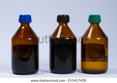 Three large glass bottles with medications. - stock photo