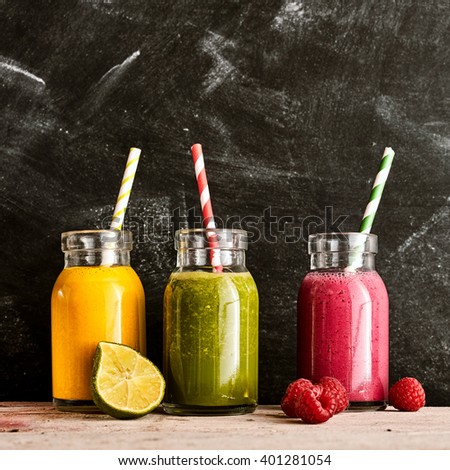 Three large mason jars of yellow green and pink tropical fruit beverages with straws on a long rustic table next to raspberries and a cut lime - stock photo