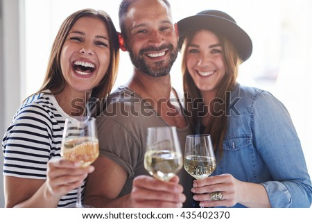 Three laughing friends in front of bright window light holding wine in glasses while celebrating something - stock photo