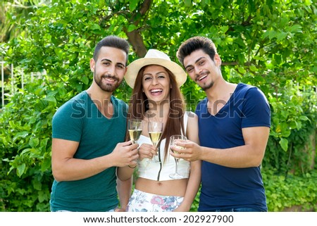 Three laughing friends standing grouped together in a leafy green garden celebrating with champagne with a trendy young woman in the center flanked by two male companions - stock photo
