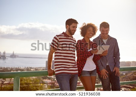 Three laughing good looking friends leaning against a railing looking at a tablet, the girl between the young men is holding