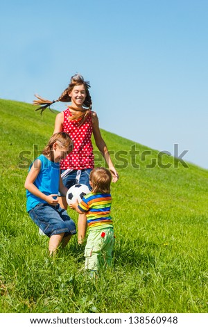 Three laughing kids playing with a ball on green grass - stock photo