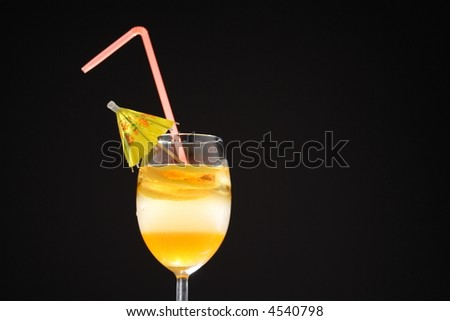 Three layer cocktail with miniature umbrella and straw - stock photo