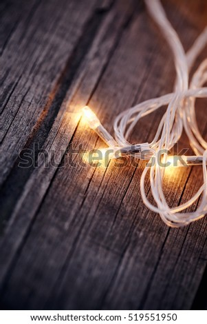 Three LED bulbs of a festive Christmas garland on a wooden background.