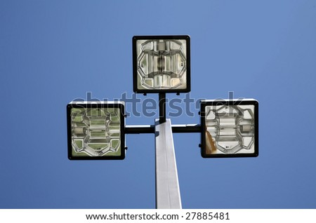 Three LED Street Lamps Affixed to an Iron Post Against a Deep Blue Sky