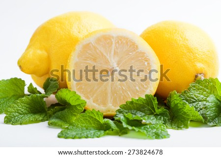 three lemon, one halved on fresh green lemon balm leaf, white background, isolated - stock photo