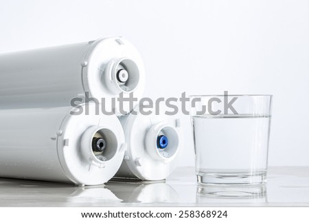 Three-level cleaning water filters and glass of water. - stock photo