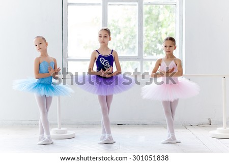 Three little ballet girls in multicolored tutu posing at ballet barre together in white studio  - stock photo