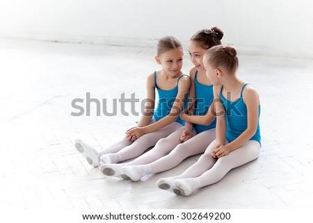 Three little ballet girls sitting in blue swimsuit and pointe shoes together on white background in ballet studio - stock photo