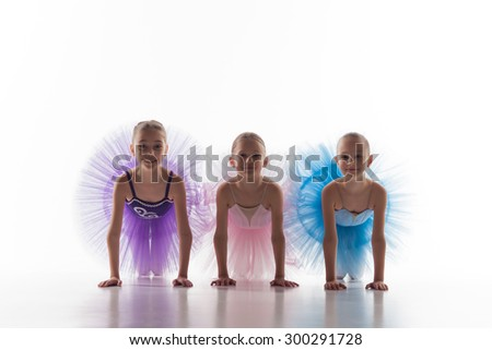 Three little ballet girls sitting in multicolored tutu and posing together on white background - stock photo
