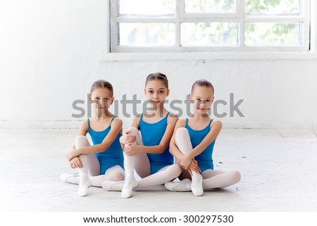 Three little ballet girls sitting in pointe shoes together on white background in ballet studio - stock photo