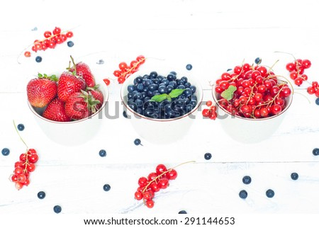 Three little bawls with different berries - strawberry, blueberry and red currants.