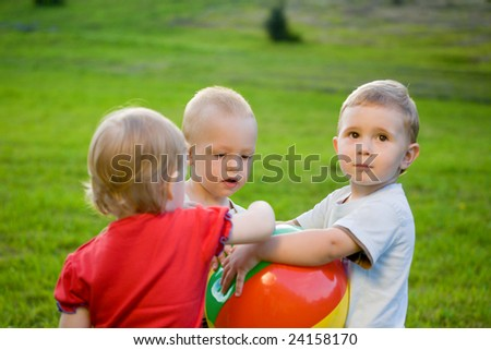 Three little boy on sunny green grass field play with ball. Focus on boy at center - stock photo