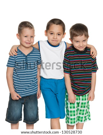 Three little boys are standing together on the white background - stock photo