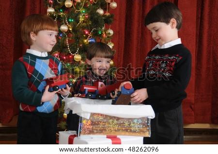 Three little boys receive a handmade wooden train as a Christmas present - stock photo