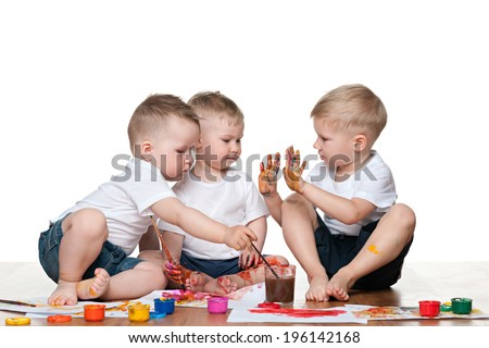 Three little boys sit on the floor and paint