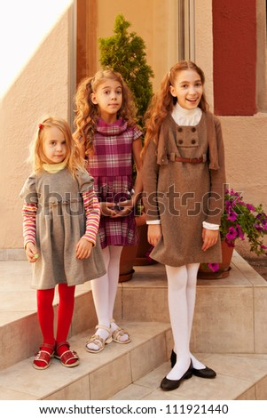 Three little caucasian sisters happy family portrait outdoor standing on school steps
