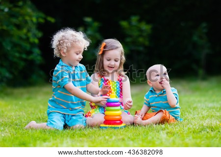 Three little children play with colorful rainbow pyramid toy. Educational toys for young child. Sibling kids building tower together. Toddler boy, preschooler girl and baby build blocks outdoors. - stock photo
