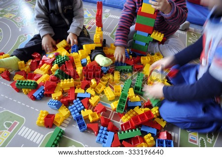 three little children playing with colored toys  - stock photo