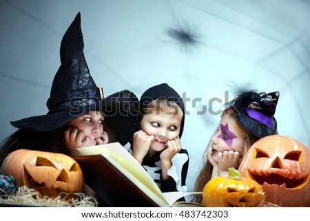 Three little children sitting together with a book among pumpkins