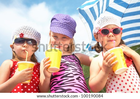 Three little cute girls drinking on the beach - stock photo