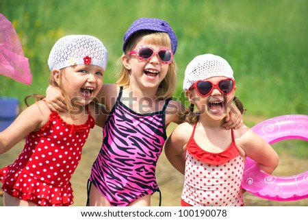 Three little cute girls go swimming in the lake - stock photo
