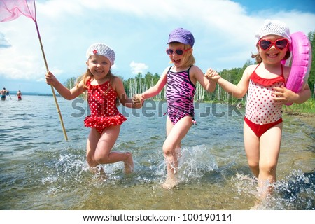 Three little funny  cute girls running on coast together - stock photo