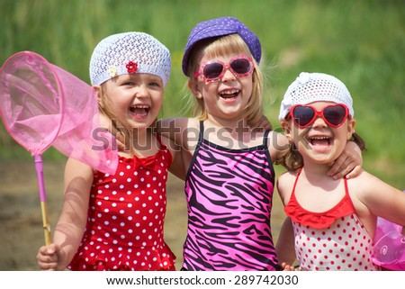 Three little girl have good time at beach - stock photo