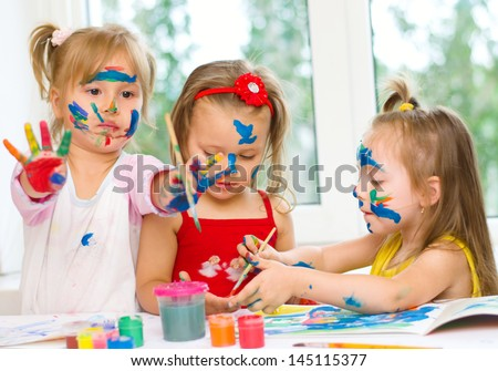 three little girls drawing with gouaches on paper