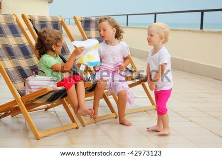 Three little girls in lounge on veranda, considering drawing - stock photo