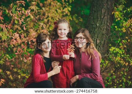 three little girls in red outfits walking in the forest  - stock photo
