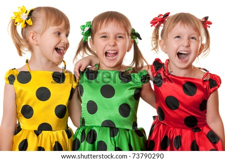 Three little girls in yellow, green and red polka dot dresses are laughing; isolated on the white background - stock photo