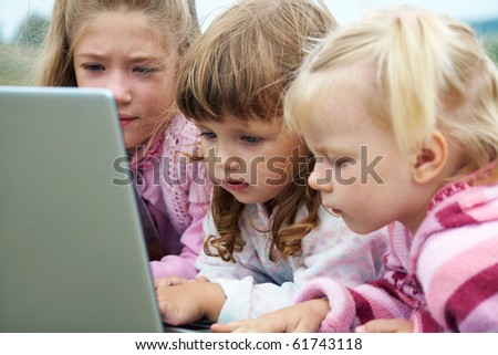 three  little girls lying on the lawn and and exercise on a laptop