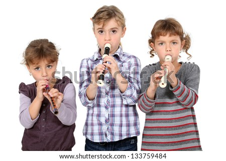 three little girls playing flute - stock photo