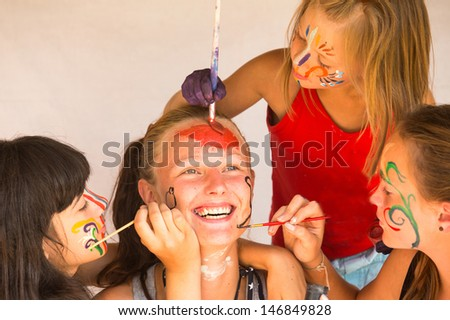 Three little girls playing with painting with sister - stock photo