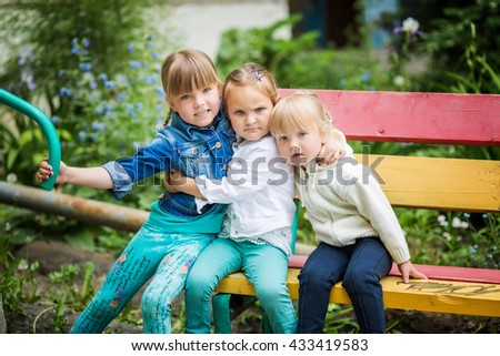 Three little girls sitting on a bench outdoors in the summer