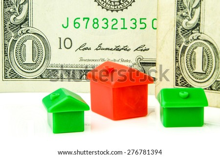 Three little green and red houses made of plastic are laying on white background with one dollar banknote  - stock photo