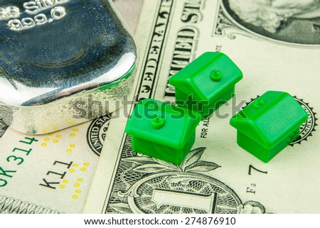 Three little green houses made of plastic and one silver brick are laying on one dollar banknote - stock photo