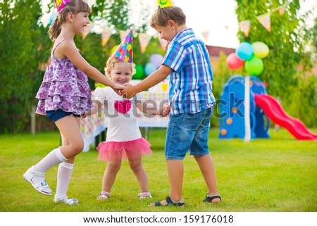 Three little kids celebrating birthday dancing roundelay - stock photo